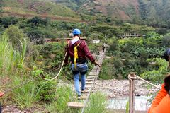 Walking the wobbly bridge. Peru jungle Stock Photography