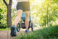 Walking woman with baby stroller enjoying summer in park royalty free stock image