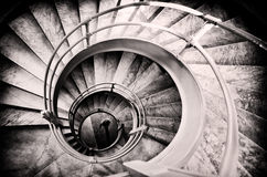 Walking woman in center of spiral stairs. In black and white with light center and burned edges Royalty Free Stock Photos