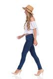 Walking Woman In Jeans, High Heels And Straw Hat Profile. Blond young woman in straw hat, jeans, white shirt walking and looking away. Side view. Full length royalty free stock image