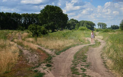 Walking woman. Lonely woman walking on country road Stock Image