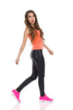 Walking Woman Sticking Out Toungue. Playful young woman in orange shirt, black leather trousers, pink sneakers walking, sticking out tongue and looking at camera Stock Photos