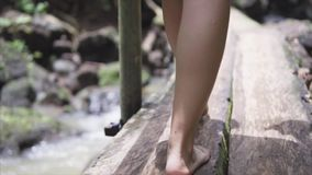 Walking woman traveling in the wild jungle forest with a dress and dirty bare foot and steps over the wet ground and. Wooden bridge over the clean mountain stock video