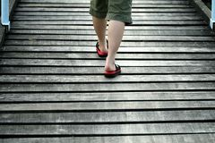 Walking on Wooden Bridge. Lady in pink slippers crossing the bridge stock photography
