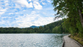 Walking on wooden path in Bled lake, Bled castle on cliff with Julian Alps and Church of the Assumption,Bled, Slovenia. Stock Photography