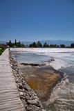 Walking on wooden pathway sightseeing of beautiful limestone hot natural turquoise springs in cotton castle, pamukkale, turkey Royalty Free Stock Photography