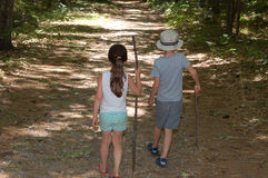 Walking through the woods. Two children walking on a trail through the woods holding walking sticks stock images