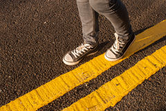 Walking on yellow street lines Royalty Free Stock Image