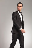 Walking young elegant man in tuxedo looking to side. Portrait of a walking young elegant man in tuxedo looking to side in studio Stock Images