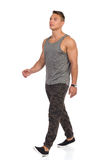 Walking Young Man In Camo Pants. Young man walking in tracksuit pants with camo, gray tank top and black sneakers. Full length studio shot isolated on white royalty free stock photo