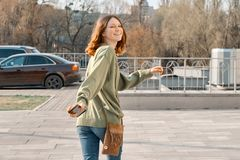 Walking young smiling girl teenager looking in camera through back with brown red hair in green sweater, sunny spring day. Background, copy space royalty free stock photography