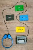 Walkman del vintage, cassetes coloridos y auriculares en el fondo de madera imágenes de archivo libres de regalías