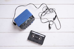 Walkman with earphones and mixtape. Vintage walkman or cassette player with earbuds and mix tape Royalty Free Stock Photo