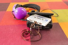 Walkman and headphones on a checkered tablecloth. Walkman with a cassette tape inside and headphones on a colorful checkered tablecloth Royalty Free Stock Photos