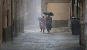 Walkng de las mujeres debajo del paraguas que lleva de las fuertes lluvias Imagen de archivo libre de regalías