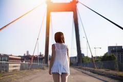 Walkong caucásico feliz joven de la mujer en el puente viejo en el parque de la ciudad al aire libre Relaje el concepto del veran Foto de archivo libre de regalías