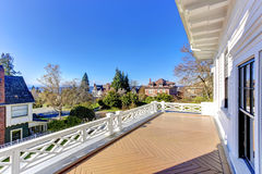 Walkout deck with low railings. Spacious walkout deck with brown wooden floor and low white railings Stock Photos