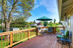 Walkout deck with patio table set and umbrella. House exterior Royalty Free Stock Images