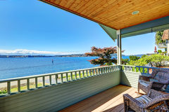 Walkout deck with wicker chairs overlooking bay. Port Orchard, W Royalty Free Stock Photo