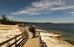 Walkpath ,Yellowstone lake, Yellowstone National park,WY,USA. People from the back, walking along the wooden walkway on the shore of Yellowstone Lake in royalty free stock photo
