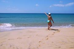 Walks along a beach. A woman walks along a beach stock image