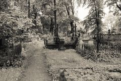 Walkway through abandoned cemetery between graves and tombs. stock photo