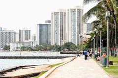 Walkway along Kuhio Beach looking toward Waikiki shops and hotels Royalty Free Stock Image