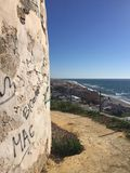 Wall of an old tower at the coast with village, blue sky and the mediterranean sea in Andalusia, Spain stock photography