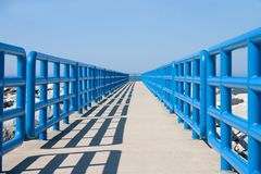 Walkway In Blue. Concrete walkway bounded by blue safety rails Stock Images
