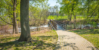 Walkway bridge in woods along the Niagara Parkway trail on a warm May spring day. Royalty Free Stock Photos