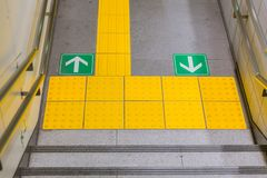 Walkway with direction arrow yellow pavement in Japan subway. Walkway with direction arrow and disabilities people yellow pavement in Japan subway Royalty Free Stock Photos