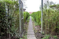 Walkway of an estate between an opened iron gate royalty free stock photo