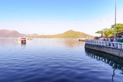 Walkway on the fateh sagar lake udaipur with boats and hills in. Walkway on the fateh sagar lake in Udaipur india in the morning. Hills and boats are visible in Royalty Free Stock Image