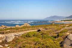 Walkway with fence along Atlantic Ocean coast with mountain on background. Portugal nature. Moss and grass on rocks at seaside. Wide beach with waves and path stock images