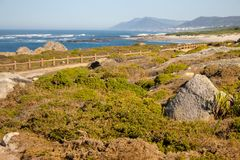Walkway with fence along Atlantic Ocean coast with mountain on background. Portugal nature. Moss and grass on rocks at seaside. Wide beach with waves and path royalty free stock image