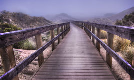 Walkway in Fog. A walkway among dunes leading to the beach on a foggy day Stock Photos