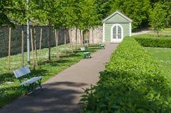 Walkway in garden between benches and green fence Stock Photos