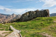 Walkway in green landscape under blue sky with white fluffy clou. Ds rock formations and mountains in a distance Royalty Free Stock Photos