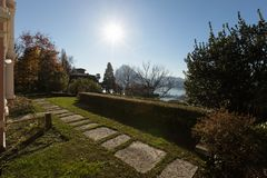 Walkway and lake. Nobody inside. Exterior of a pink vintage villa with garden and driveway consisting of small stones Royalty Free Stock Image