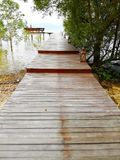 The walkway is made of wood. There is a way out to the waterfront, and at the end, there seats that extend out to sea. The side o royalty free stock photography