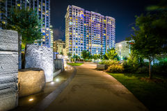 Walkway and modern buildings at night, seen at Romare Bearden Pa. Rk, in Uptown Charlotte, North Carolina Stock Photos