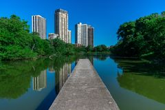North Pond in Chicago during Summer. The walkway at North Pond extending out towards the water with residential building reflections during summer stock images