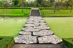 Walkway over canal into garden Stock Image