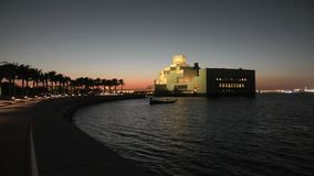 Doha Park at sunset. The walkway with palm trees along Doha Bay. Museum and dhow at sunset sky. Scenic urban cityscape. Qatari capital in Middle East, Arabian stock video footage
