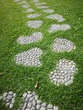 Walkway in the park Scree Pebbles mix cement placed on the grass free from pattern material pavement sidewalk pathway passageway a. Walkway in the park Scree stock image
