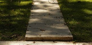 The Walkway. A paved walkway cuts between grass of a front yard and between light and shadow Royalty Free Stock Photography