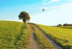 Walkway through rural landscape, hotair balloon Stock Photos