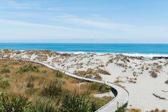 Walkway on sand beach with seacoast stock image