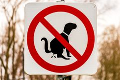Walkway sign prohibiting the dogs to do their needs. In a park Royalty Free Stock Photos