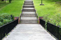 Walkway and steps up a grassy hill. Stock Photography